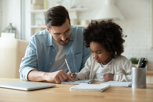 Caring Dad Help Biracial Daughter With Homework At Home Stock Photo - Download Image Now