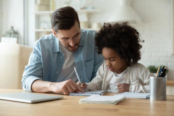 pflege vater helfen biracial tochter mit hausaufgaben zu hause - homeschooling stock-fotos und bilder