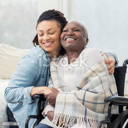 932074776istockphoto Caring daughter hugs wheelchair-bound mother 932074802