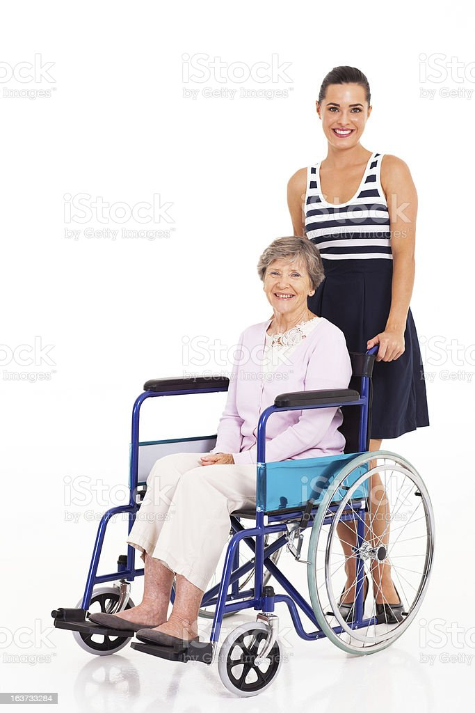 caring daughter pushing senior mother on wheelchair royalty-free stock photo