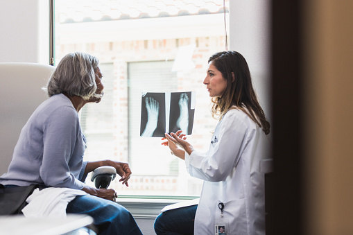 A serious female orthopedic doctor shows a senior female patient an x-ray of the patient's fractured foot.
