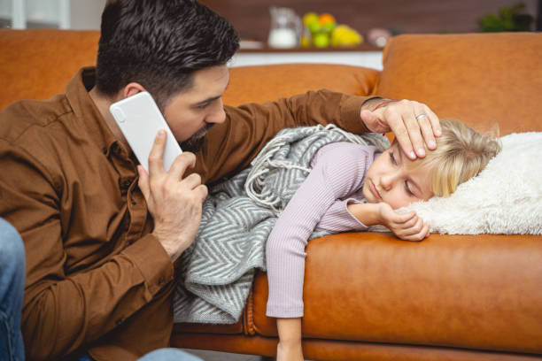 Caring father calling doctor and touching daughter forehead stock photo