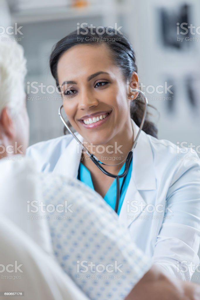 Caring female doctor examines senior male patient stock photo