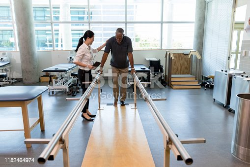 Female physical therapist helps a senior man walk following a stroke. The man is using parallel bars in a rehab center.