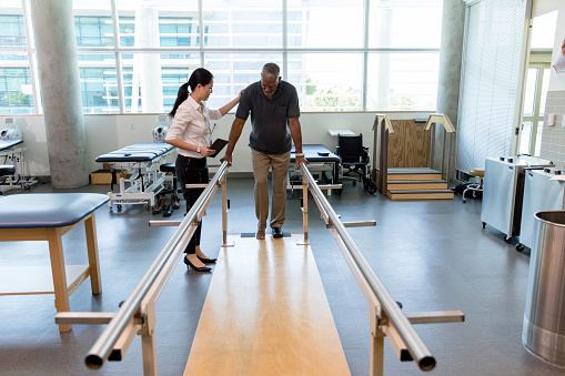 950649706 istock photo Caring female physical therapist helps stroke victim in rehab center 1182464974