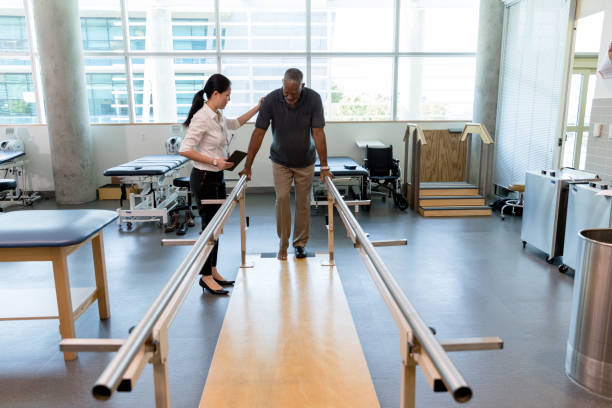Caring female physical therapist helps stroke victim in rehab center Female physical therapist helps a senior man walk following a stroke. The man is using parallel bars in a rehab center. recovery stock pictures, royalty-free photos & images