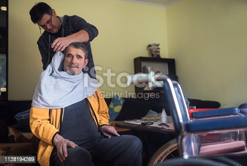 Volunteer in home visit at senior man,cares about his hygiene