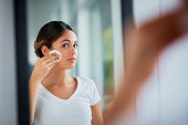 Shot of an attractive young woman cleaning her face with cotton wool in the bathroom