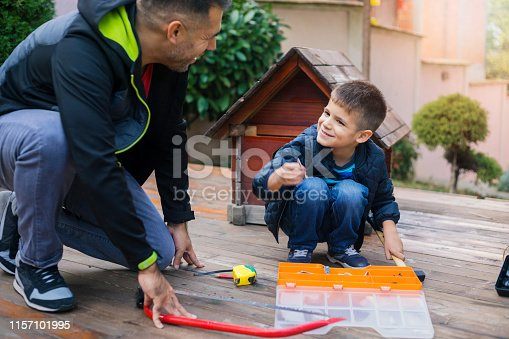 Cheerful father and son have a fun and building dogs house for their pet at formal garden