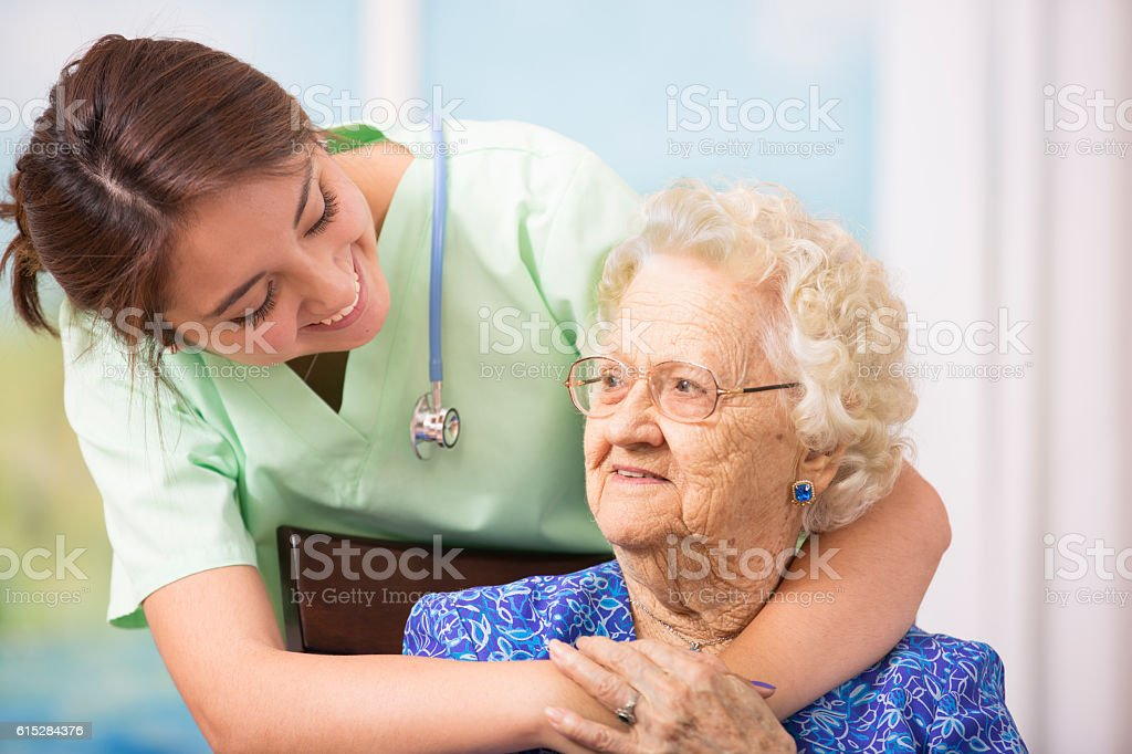 Caring, hispanic nurse gives senior patient a reassuring hug in...