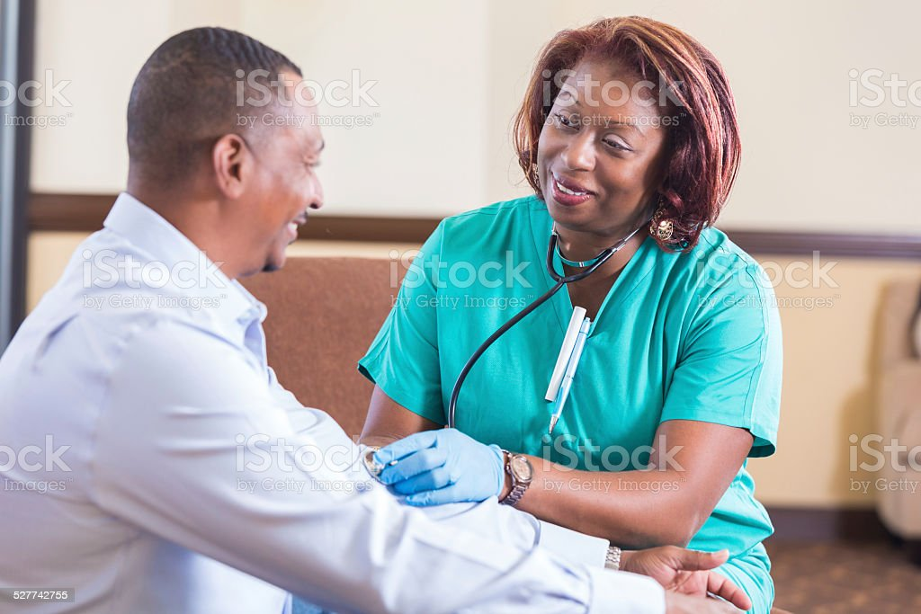 Caring home healthcare nurse checking blood pressure of mature patient stock photo