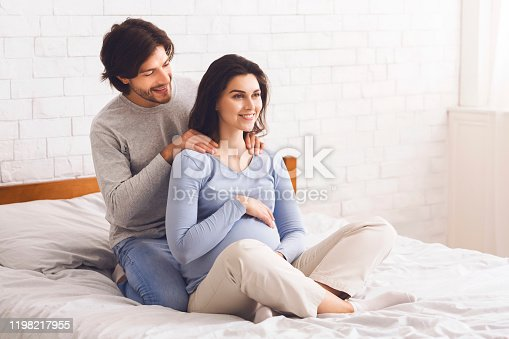 istock Caring husband doing massage to his happy pregnant wife 1198217955