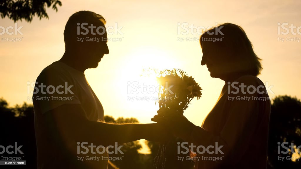 Caring man presenting flowers to woman at sunset, wedding...