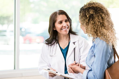 A caring mature female doctor smiles as she gives good news to a female patient about the patient's test results.