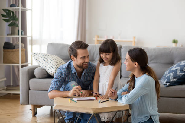 Caring mom and dad teaching little daughter to draw Happy family with kid playing together, caring mom and dad smiling teaching little daughter to draw with color pencils, mother and father having fun with cute child help in creative weekend activity parent stock pictures, royalty-free photos & images