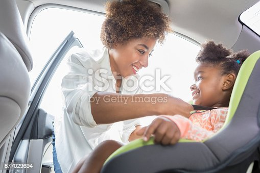 Young African American mom smiles while strapping her daughter into a booster seat.