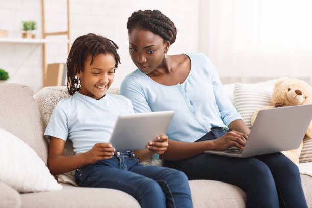 Caring mom providing children's online privacy protection Parental Control. Black mother watching her daughter's activity online. Copy space shock tactics stock pictures, royalty-free photos & images