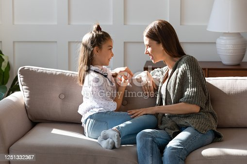 1070262182 istock photo Caring mother and little daughter chatting, sitting on cozy couch 1251332367