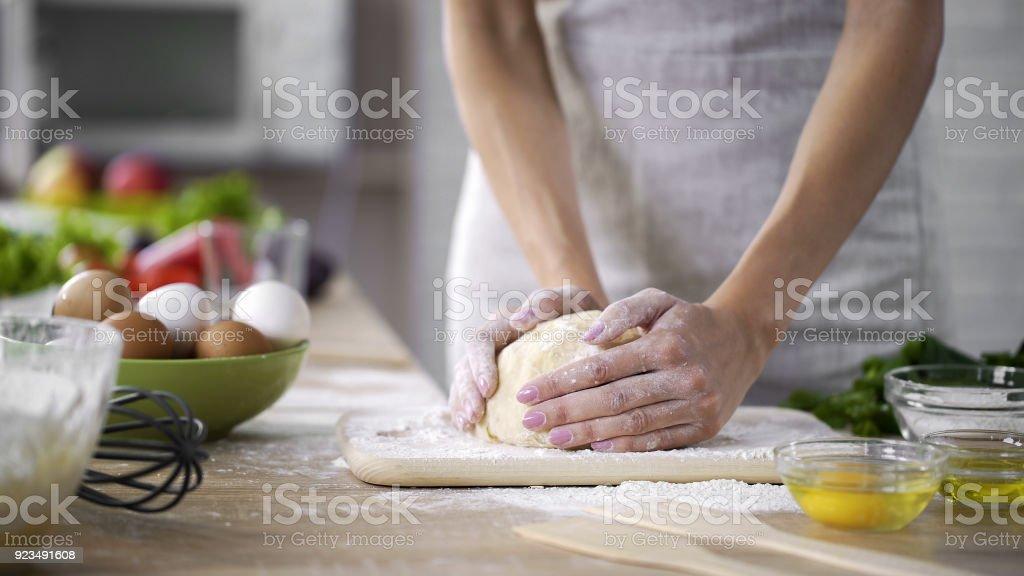 Fürsorgliche Mutter kneten den Teig in der Küche, Frau, die Herstellung von Kuchen, Draufsicht – Foto