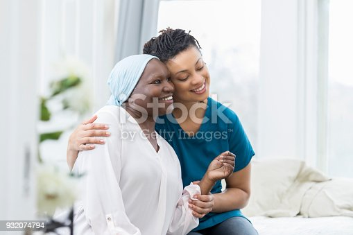 istock Caring nurse comforts elderly female patient 932074794