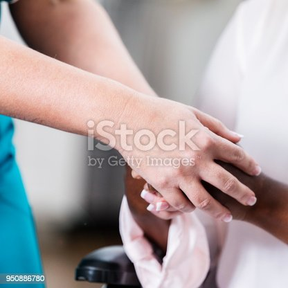 932074762istockphoto Caring nurse comforts senior female patient 950886780