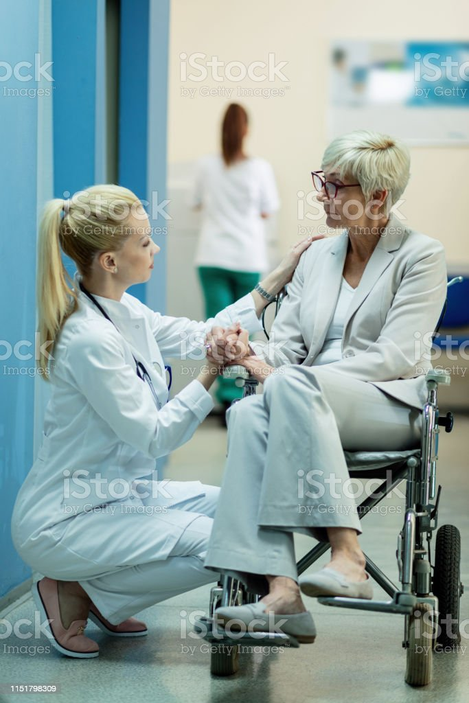 Disabled senior woman in wheelchair holding hands with a doctor while...