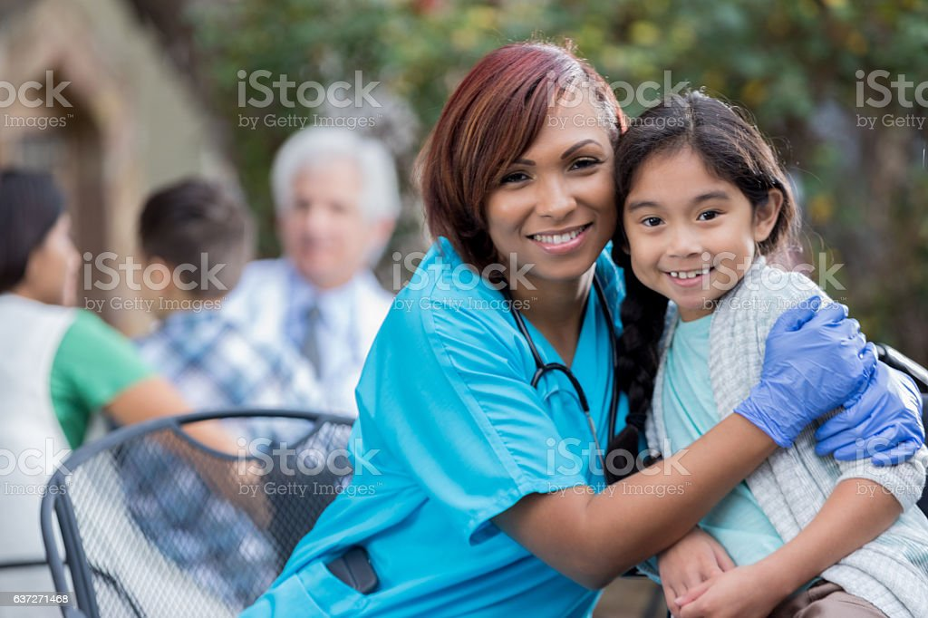 Caring nurse hugs young female Asian patient stock photo