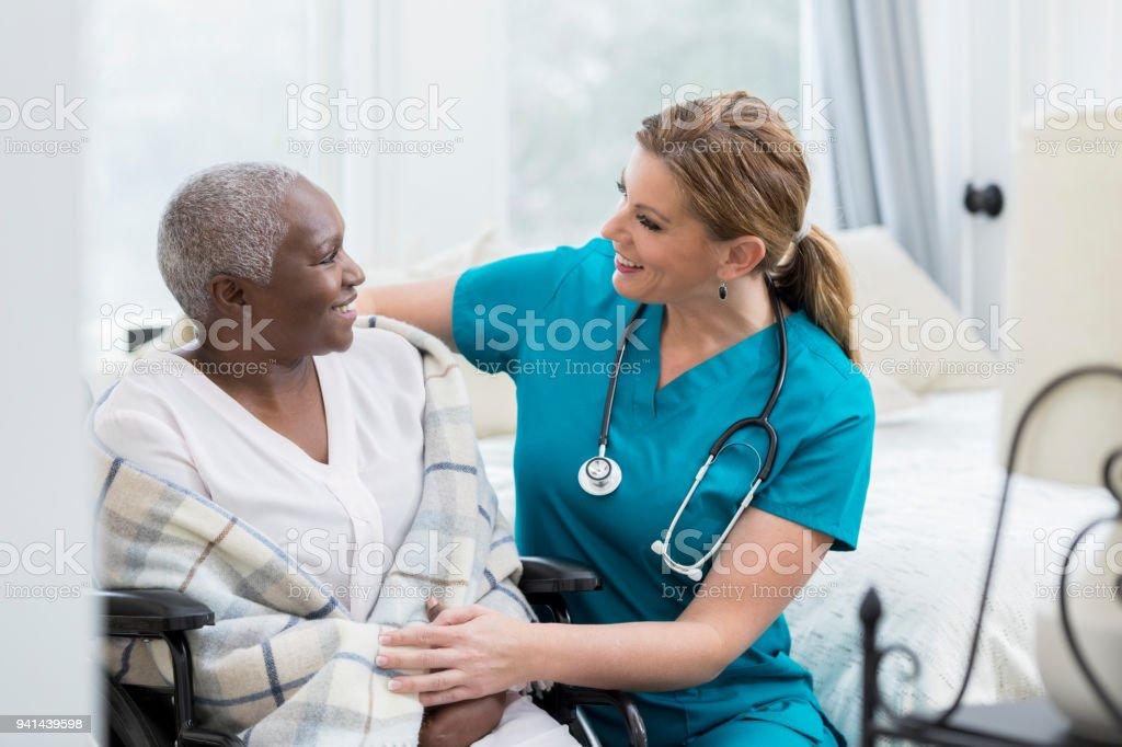 Caring nurse talks with senior female patient stock photo