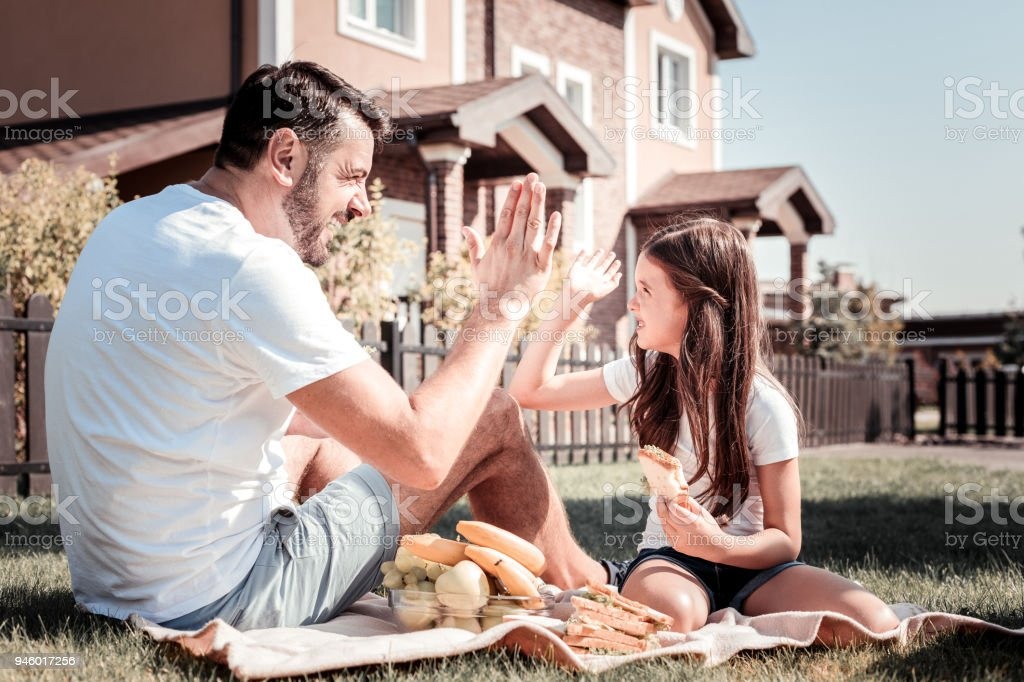 Caring pleasant father smiling and spending time with daughter. stock photo
