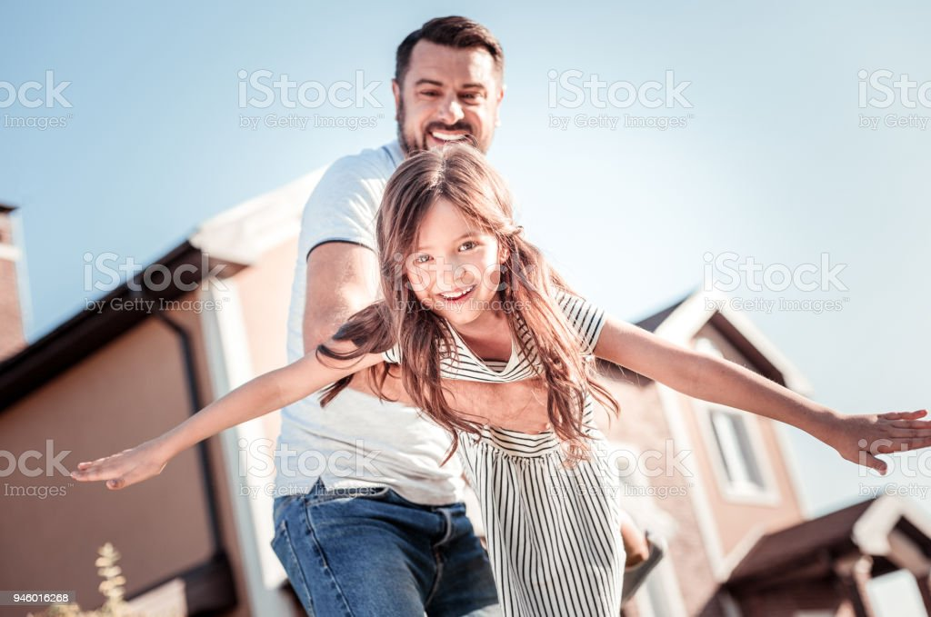 Caring pleasant father smiling and supporting his daughter. stock photo