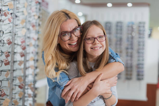 Caring positive mother embracing her smiling daughter stock photo