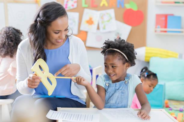 fürsorgliche vorschullehrerin hilft mädchen in der klasse - schöne englische wörter stock-fotos und bilder