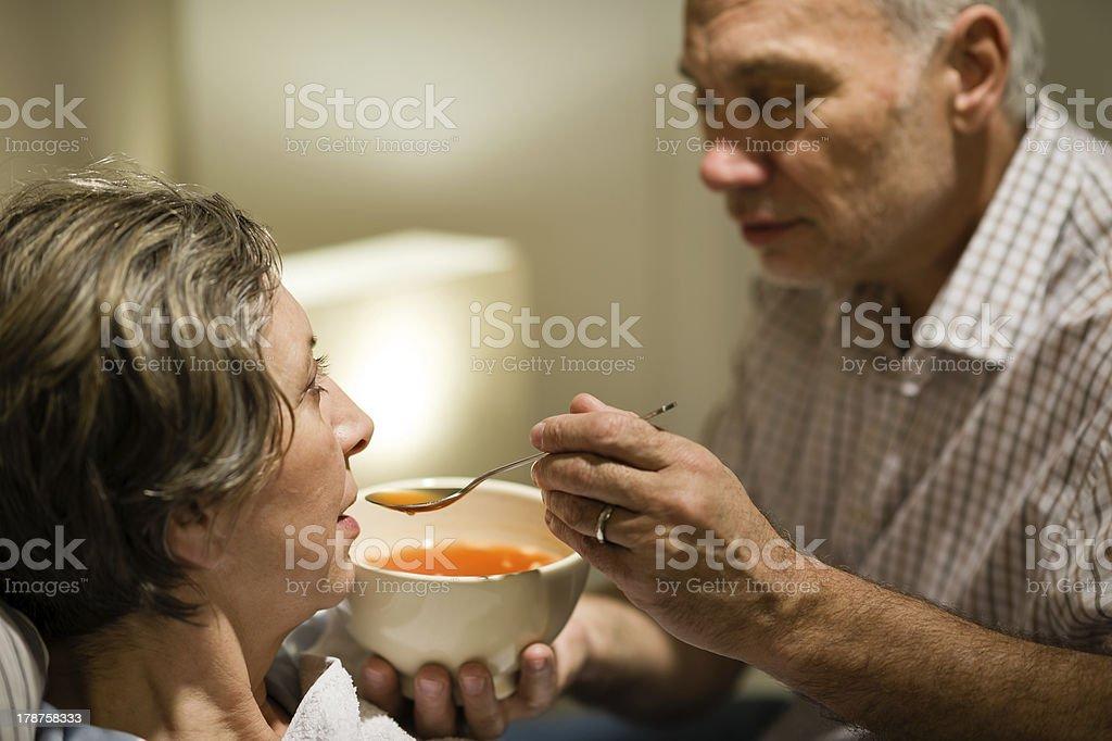 Caring senior man feeding his sick wife stock photo