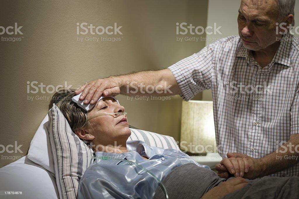 Caring senior man helping his sick wife stock photo