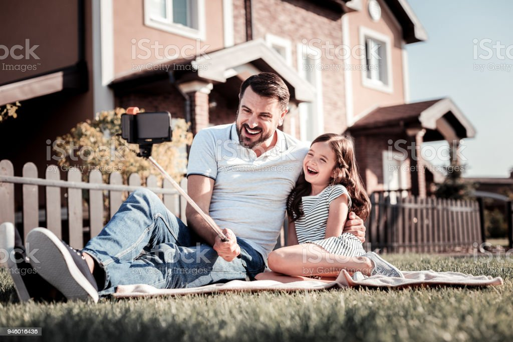Caring unshaken father sitting and holding monopode. stock photo
