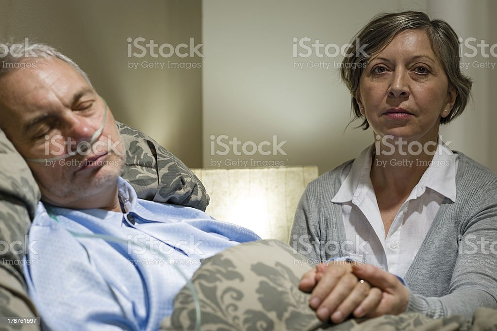Caring wife holding sick senior husband's hands stock photo