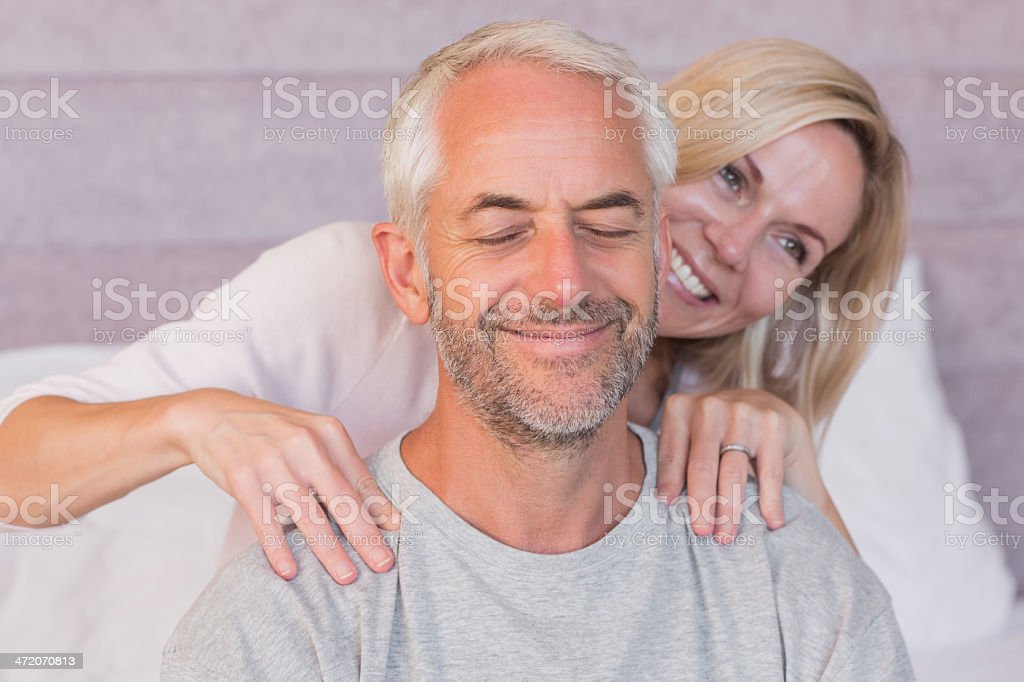 Caring woman giving massage to her smiling husband royalty-free stock photo