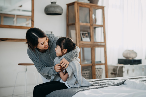 Caring young Asian mother putting a coat on her daughter at home