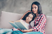 Caring young mother in casual clothes is reading a story from a book to her cute and lovely schoolgirl daughter is sleeping on her mother's shoulder, they are sitting on a sofa