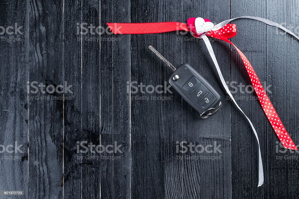 Cark key with a red ribbon on black wooden table. stock photo