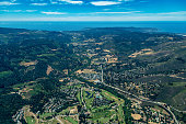 Tha aerial view of Carmel river valley in Northern California with hills around it and Pacific ocean in the distance,