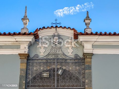 Top of the beautiful entrance gate at Carmo Cemetery in São João del Rei, decorated with a wrought iron cross, a skull and relief flower vases.  In the background, the blue sky with a cloud that looks like it is coming out of the cross.