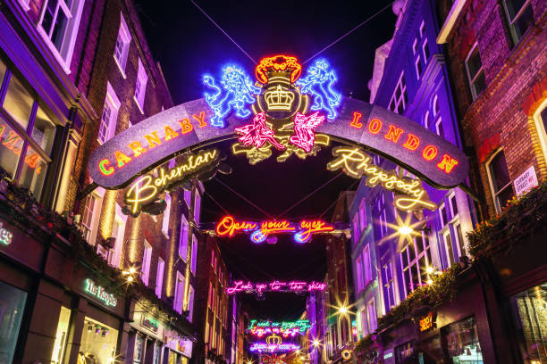 Carnaby Street, Christmas shopping, London London, United Kingdom - November 18, 2018: Crowds of Christmas shoppers in Carnaby Street, Central London. Long exposure at night of Carnaby Street, a retail district in London famous for it's fashion and lifestyle shops. carnaby street stock pictures, royalty-free photos & images