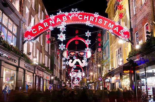 Carnaby Street, Christmas shopping, London London, United Kingdom - December 13, 2014: Crowds of Christmas shoppers in Carnaby Street, Central London. Long exposure at night of Carnaby Street, a pedestrianised retail district in London famous for it's fashion and lifestyle shops. carnaby street stock pictures, royalty-free photos & images