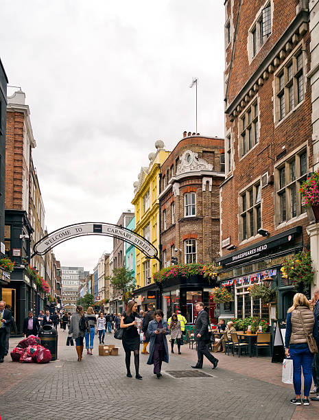 Carnaby Street, London London, England - September 8, 2015: Tourists and shoppers in Carnaby Street, Central London, on an overcast day. Carnaby Street became famous in the 1960s for its large number of shops stocking Mod, secondhand and hippie clothing. It is one of the most well known streets to be visited by tourists to London. carnaby street stock pictures, royalty-free photos & images