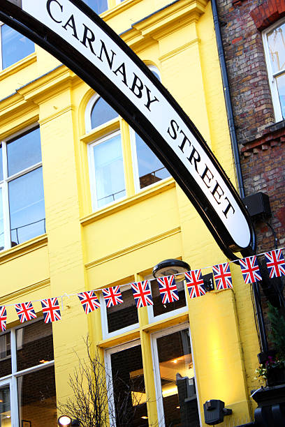 Carnaby Street, London Sign and British flags in the popular Carnaby Street in London, UK. carnaby street stock pictures, royalty-free photos & images