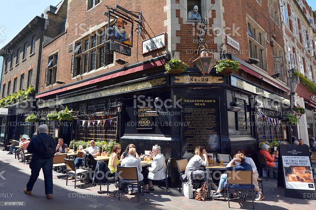 Carnaby Street London UK London, United Kingdom - May 14, 2015: People drink at Shakespeares Head pub in Carnaby Street London UK. Carnaby Street is a popular pedestrianized shopping street in the City of Westminster, London Architecture Stock Photo