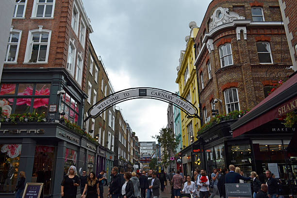 Carnaby Street London, UK - September 13, 2014: view down Carnaby Street with shoppers in London, UK. It is an iconic fashion street in the Soho district famous in the 1960s for mods and hippies. carnaby street stock pictures, royalty-free photos & images