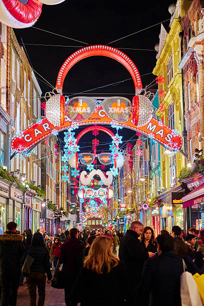 Carnaby Street London, UK- December 20, 2014: Nighttime shot of busy Carnaby street with Christmas decoration in the shape of headphones along the street. December 20, 2014 in London. carnaby street stock pictures, royalty-free photos & images