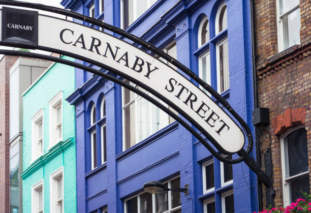 Carnaby Street sign - iconic London shopping street Colourful buildings behind the curving sign for Carnaby Street, a street with a long history as a fashion destination. carnaby street stock pictures, royalty-free photos & images